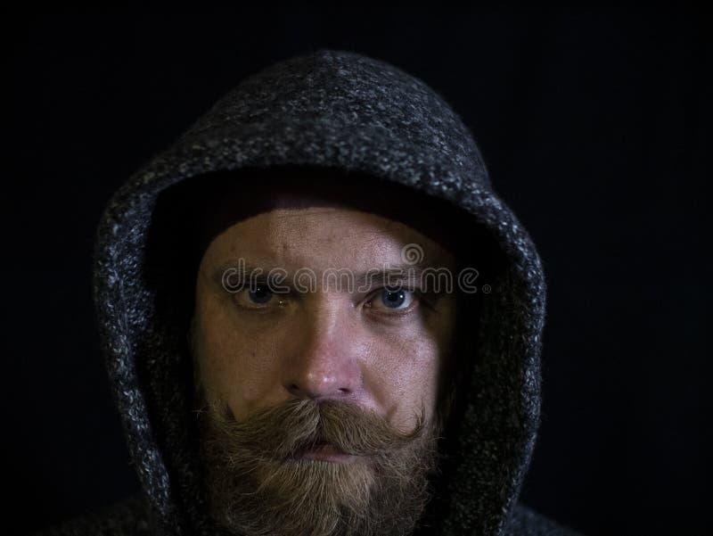 Ritratto di un uomo con una barba e dei baffi nel cappuccio con un fronte serio su un fondo nero fotografia stock