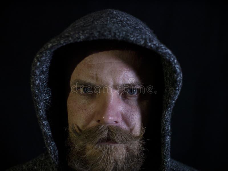 Ritratto di un uomo con una barba e dei baffi nel cappuccio con un fronte serio su un fondo nero immagine stock libera da diritti