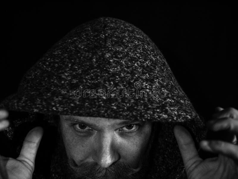 Ritratto di un uomo con una barba e dei baffi nel cappuccio con un fronte serio su un fondo nero Foto in bianco e nero di Pechino fotografia stock
