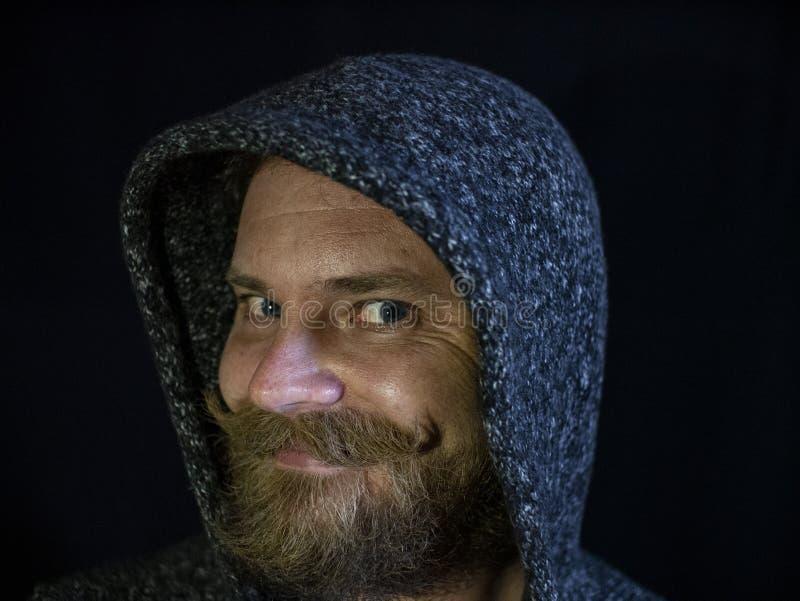 Ritratto di un uomo con una barba e dei baffi nel cappuccio con un fronte sorridente su un fondo nero fotografia stock