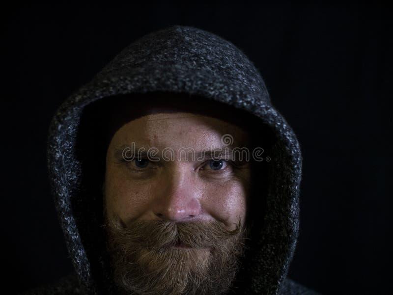 Ritratto di un uomo con una barba e dei baffi nel cappuccio con un fronte sorridente su un fondo nero fotografie stock