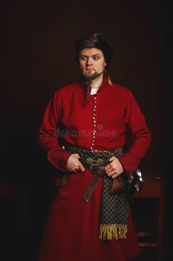Ritratto di un uomo in un costume medievale su un fondo scuro Vestiti della piccola nobiltà polacca fotografia stock libera da diritti