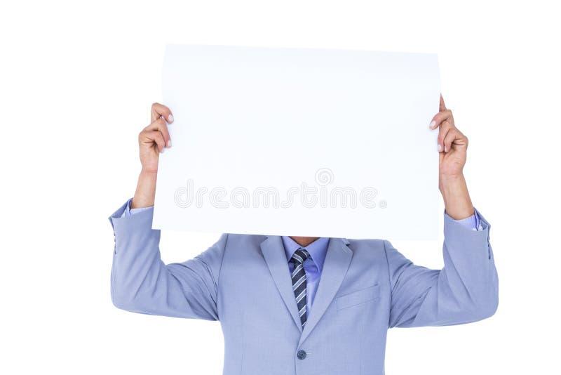 Ritratto di un uomo d'affari che nasconde il suo fronte dietro un pannello in bianco fotografie stock libere da diritti