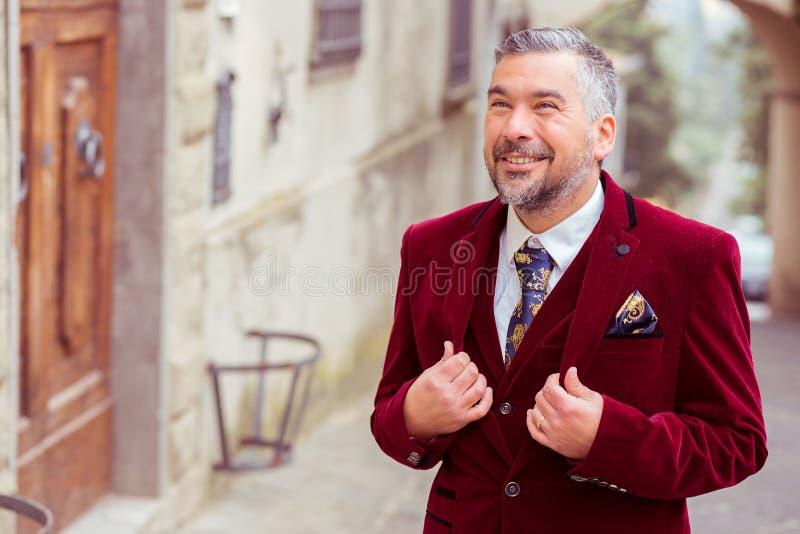 Ritratto di un uomo elegante di affari di medio evo che sta all'aperto su una via di vecchio villaggio fotografie stock libere da diritti