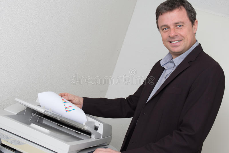 Ritratto di un uomo felice di affari che per mezzo della macchina immagini stock