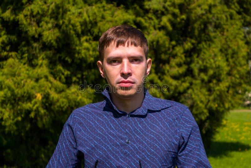 Ritratto di un uomo nell'esterno diritto della camicia blu in parco fotografia stock libera da diritti
