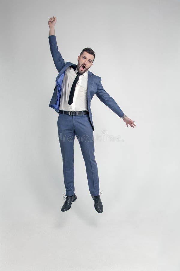 Ritratto di un uomo pazzo divertente e piccolo dell'uomo d'affari che salta alto e che incoraggia su un fondo bianco fotografia stock