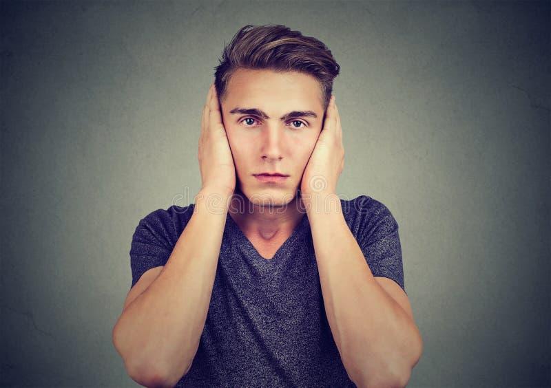 Ritratto di un uomo rilassato che copre le sue orecchie che esaminano macchina fotografica Non senta concetto diabolico Emozioni  fotografia stock libera da diritti