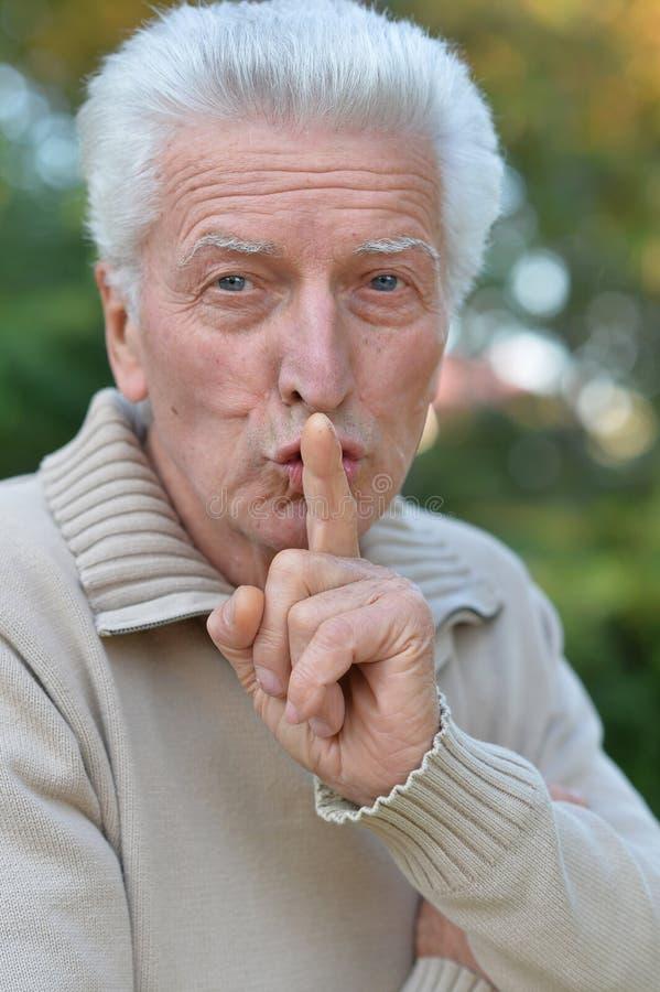 Ritratto di un uomo senior con il dito sulle labbra che gesturing silenzio immagini stock