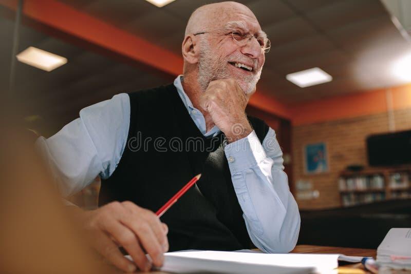Ritratto di un uomo senior sorridente che si siede in una biblioteca immagine stock libera da diritti