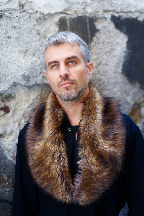 Ritratto di un uomo sexy in pelliccia del lupo e dell'espressione premurosa sul suo fronte, una parete della struttura su fondo immagini stock