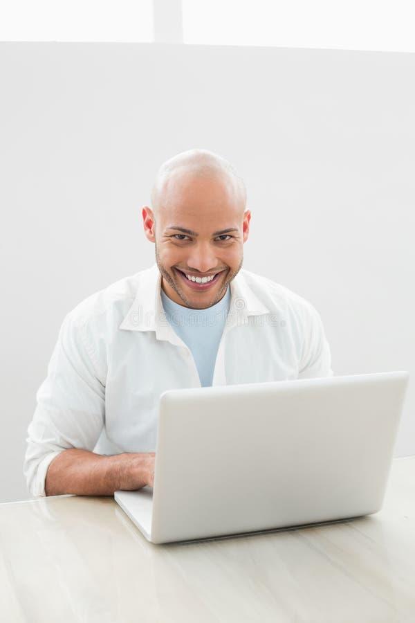 Ritratto di un uomo sorridente casuale che per mezzo del computer portatile allo scrittorio immagine stock libera da diritti