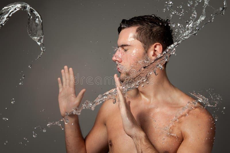 Ritratto di un uomo sotto i getti di acqua fotografia stock
