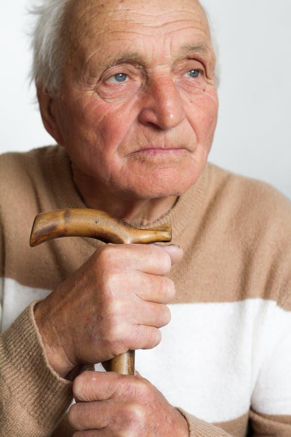 Ritratto di un uomo triste anziano che ha messo la sua testa sulla maniglia di una canna di legno immagini stock libere da diritti