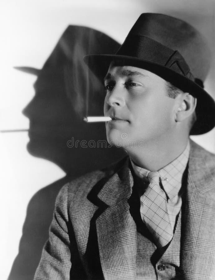 Ritratto di un uomo in una fedora con una sigaretta nella sua bocca (tutte le persone rappresentate non sono vivente più lungo e  fotografia stock