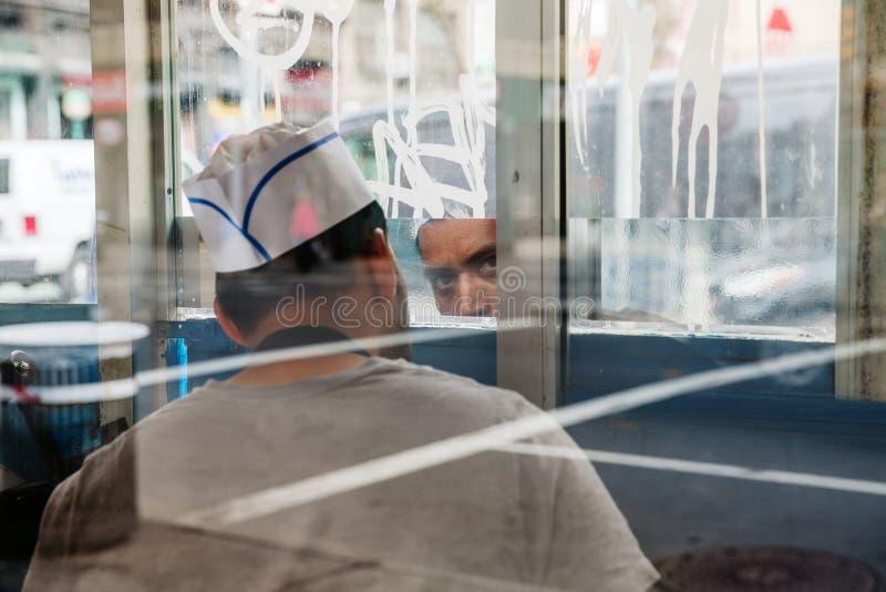 Ritratto di un venditore ad un chiosco degli alimenti a rapida preparazione in Manhattan fotografie stock