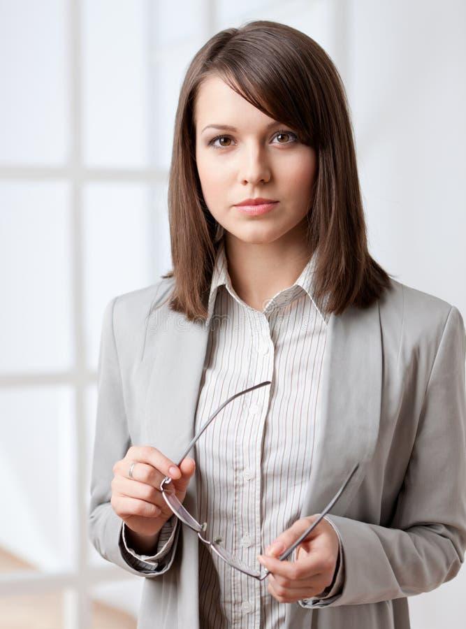 Ritratto di un vetro passante della donna di affari bella immagine stock libera da diritti
