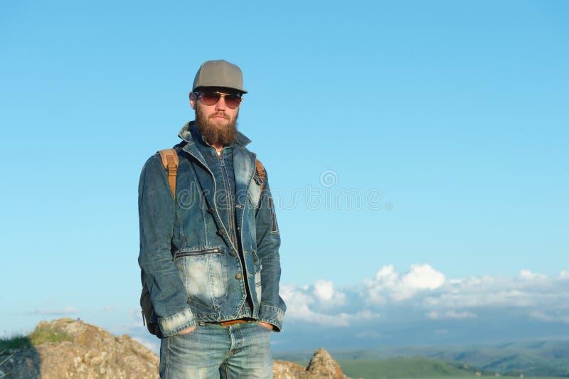 Ritratto di un viaggiatore alla moda barbuto in un cappuccio contro un cielo blu Tempo di viaggiare concetto immagini stock libere da diritti