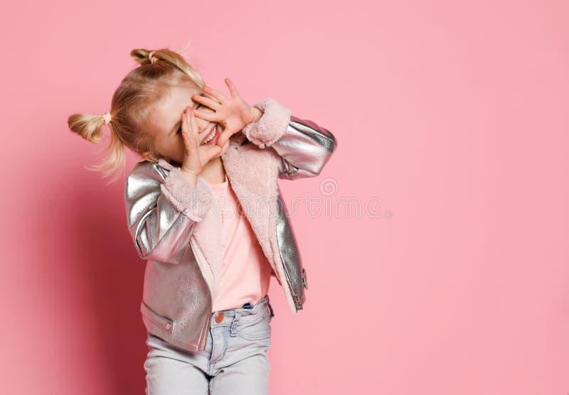 Ritratto di una bambina in abbigliamento alla moda che si siede sul fondo rosa e che gioca su fotografia stock