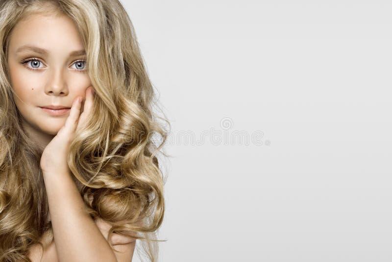 Ritratto di una bambina adorabile con capelli lunghi su un fondo bianco nello studio immagini stock libere da diritti