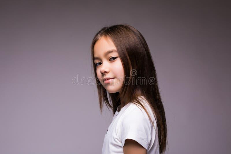 Ritratto di una bambina castana affascinante, isolato su fondo marrone fotografia stock