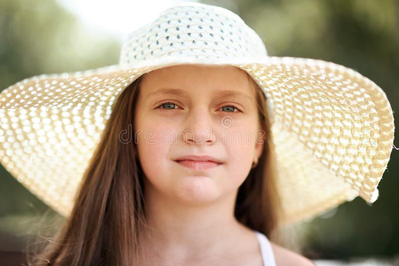 Ritratto di una bambina che indossa un grande cappello, un bello giorno soleggiato, un sole luminoso e le ombre, primo piano del  fotografia stock libera da diritti