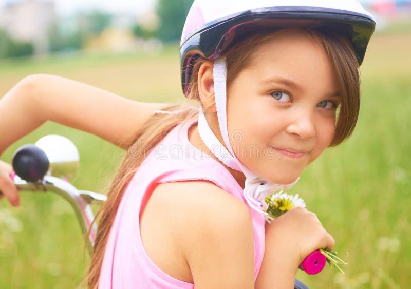 Ritratto di una bambina divertente allegra in un casco di sicurezza rosa sulla sua bici immagine stock libera da diritti