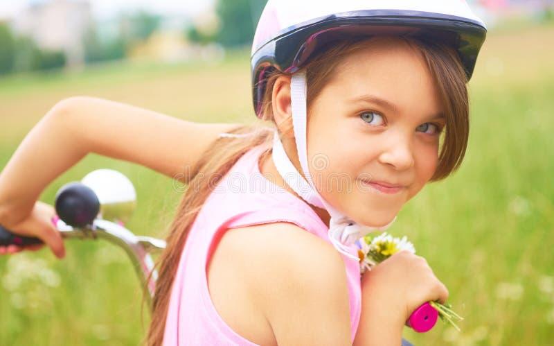 Ritratto di una bambina divertente allegra in un casco di sicurezza rosa sulla sua bici immagine stock