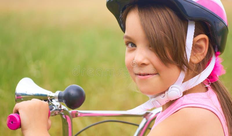 Ritratto di una bambina divertente allegra in un casco di sicurezza rosa sulla sua bici immagini stock