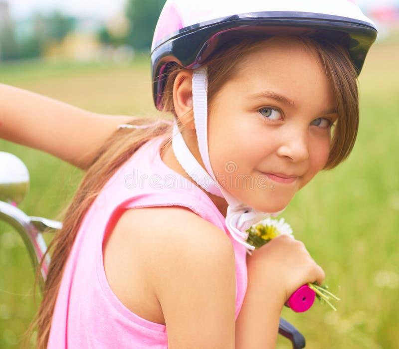 Ritratto di una bambina divertente allegra in un casco di sicurezza rosa sulla sua bici fotografia stock libera da diritti
