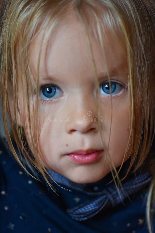 Ritratto di una bambina romantica triste con i grandi occhi azzurri dall'Europa Orientale, primo piano, fondo scuro fotografia stock libera da diritti