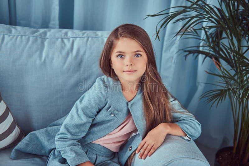 Ritratto di una bambina sveglia che porta un vestito alla moda, sedendosi su un sofà a casa, esaminando una macchina fotografica immagine stock