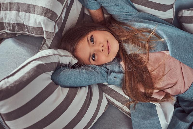 Ritratto di una bambina sveglia con capelli marroni lunghi, l'occhiata perforante ed il sorriso affascinante, esaminando una macc immagine stock libera da diritti