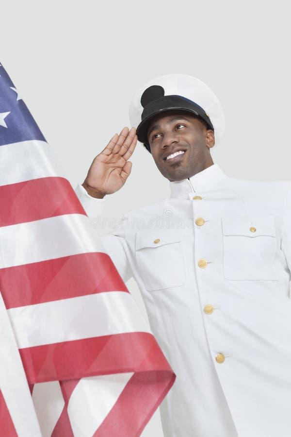 Ritratto di una bandiera americana di saluto del giovane ufficiale felice della marina statunitense sopra fondo grigio fotografie stock