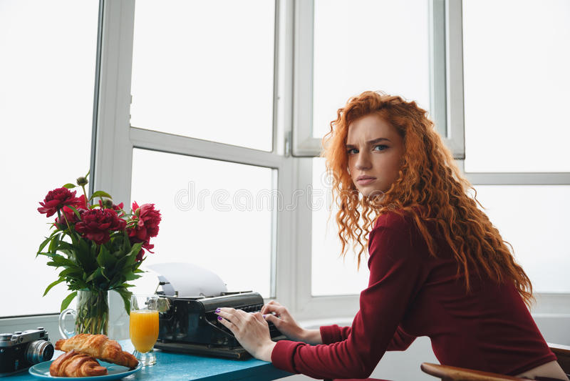 Ritratto di una battitura a macchina della donna seriousredheaded giovani immagine stock
