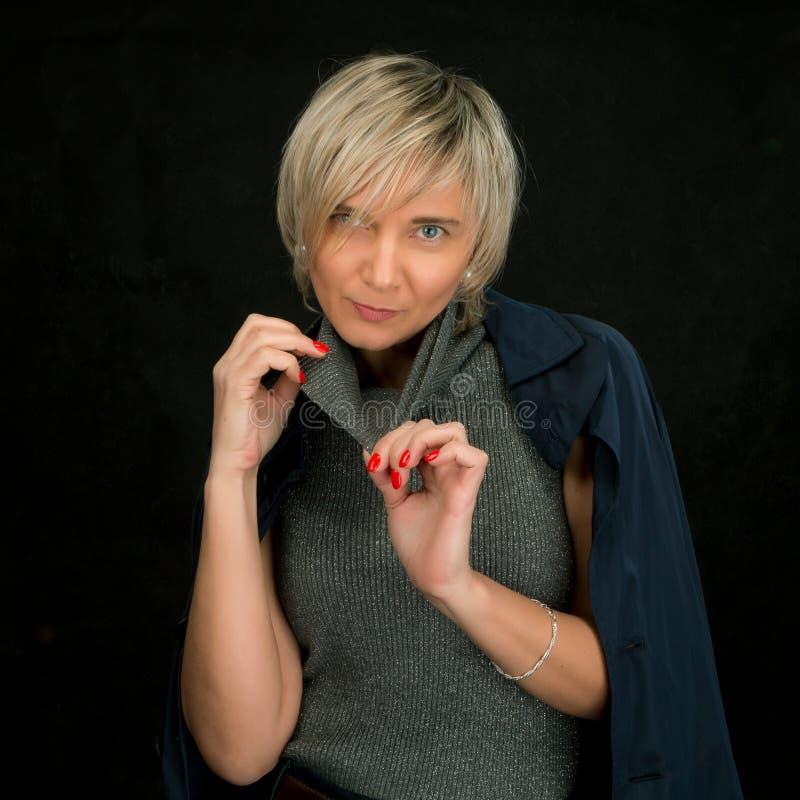 Ritratto di una bionda con un taglio di capelli nello studio su un fondo scuro, bella donna moderna luxuriously vestita 40+ fotografia stock libera da diritti