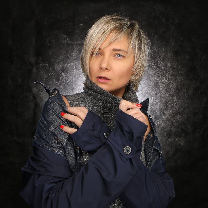 Ritratto di una bionda con un taglio di capelli nello studio su un fondo scuro, bella donna moderna luxuriously vestita 40+ fotografia stock