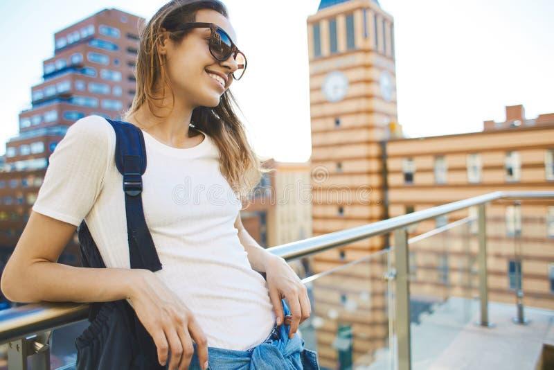 Ritratto di una città di camminata della giovane donna attraente al giorno soleggiato fotografia stock