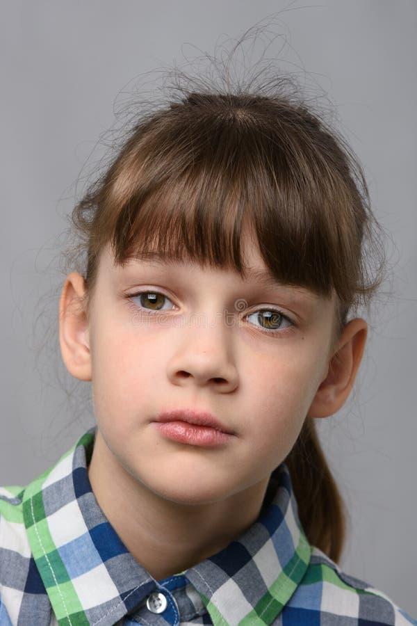 Ritratto di una compassionevole bambina di dieci anni di apparenza europea, da vicino immagine stock libera da diritti