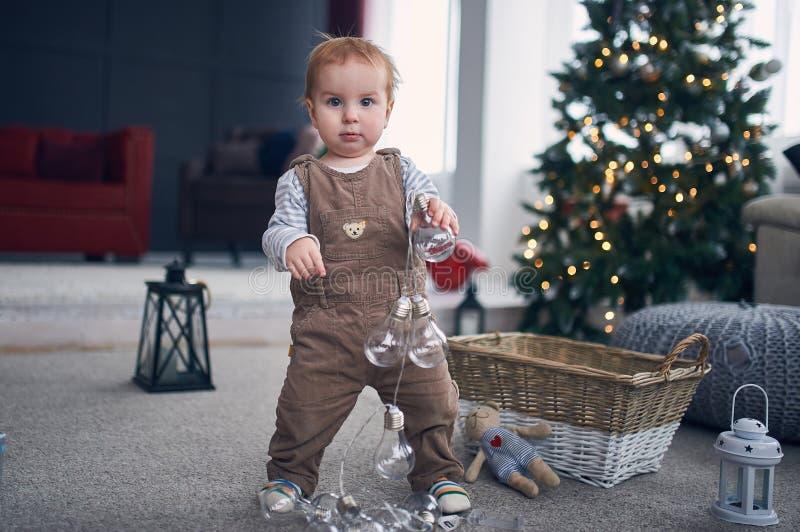 Ritratto di una condizione di 1 anno sveglia del neonato sul pavimento il concetto dei primi punti decorazioni di natale su un fo immagine stock