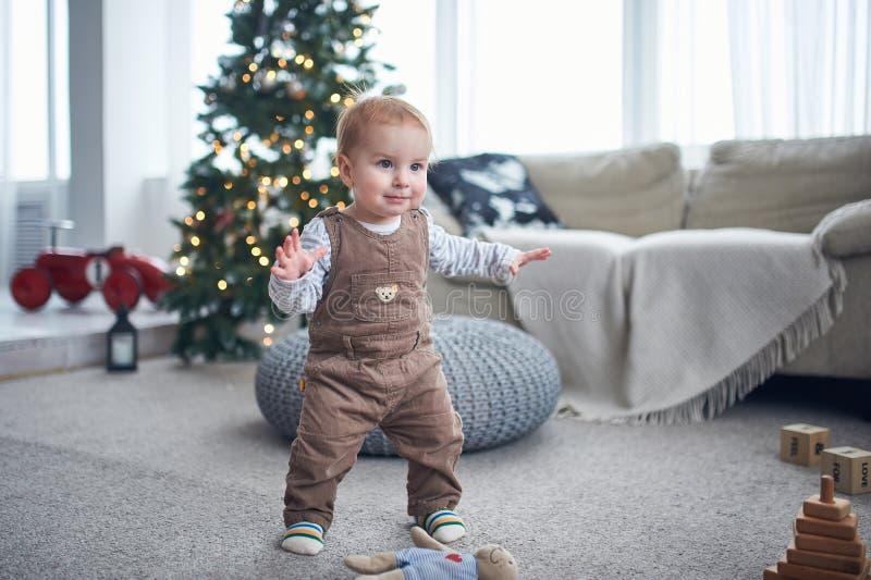 Ritratto di una condizione di 1 anno sveglia del neonato sul pavimento il concetto dei primi punti decorazioni di natale su un fo immagine stock libera da diritti