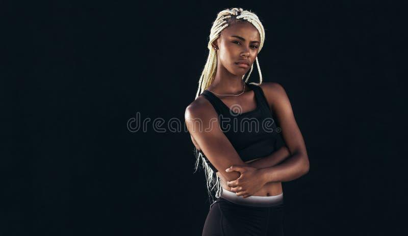 Ritratto di una condizione dell'atleta femminile contro il fondo nero immagine stock libera da diritti
