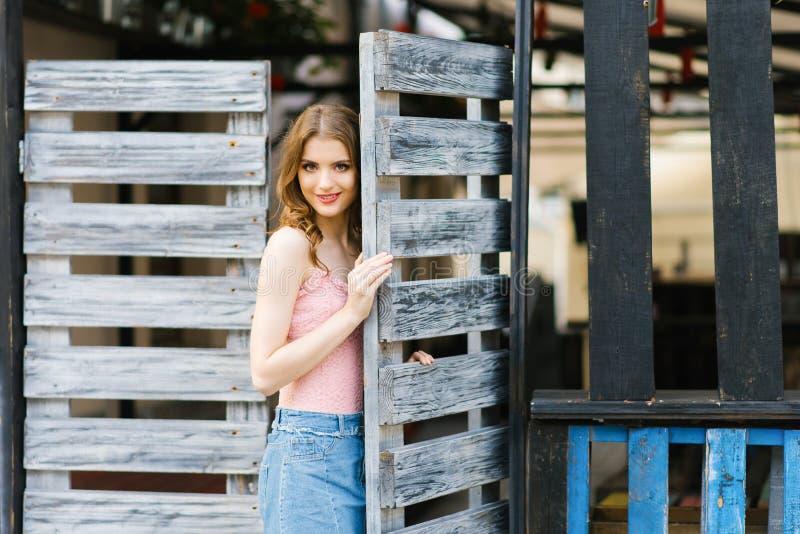 Ritratto di una condizione graziosa e bella della ragazza in un portone di legno Il concetto di nuova vita, l'entrata a qualche c fotografie stock