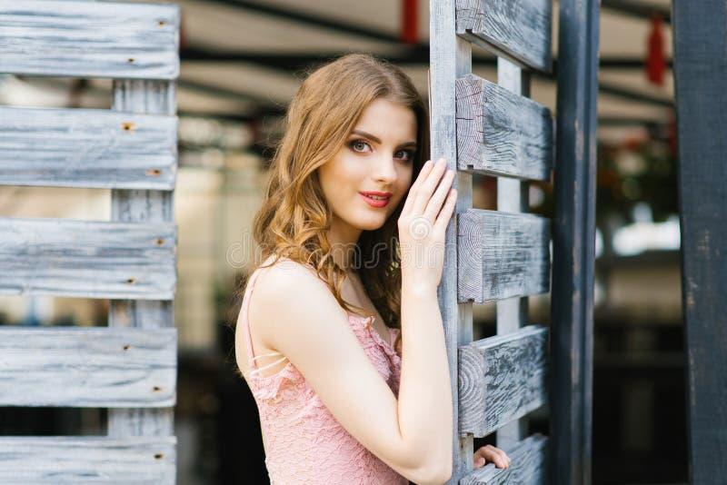 Ritratto di una condizione graziosa e bella della ragazza in un portone di legno Sorriso misterioso e seducente immagine stock