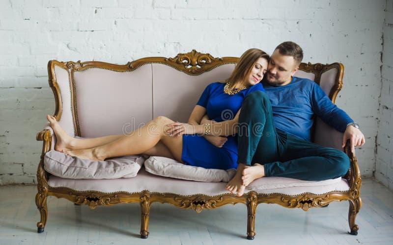 Ritratto di una coppia alla moda alla moda che si siede insieme ai piedi nudi sullo strato nel salone, abbracciando, sorridendo, fotografia stock libera da diritti