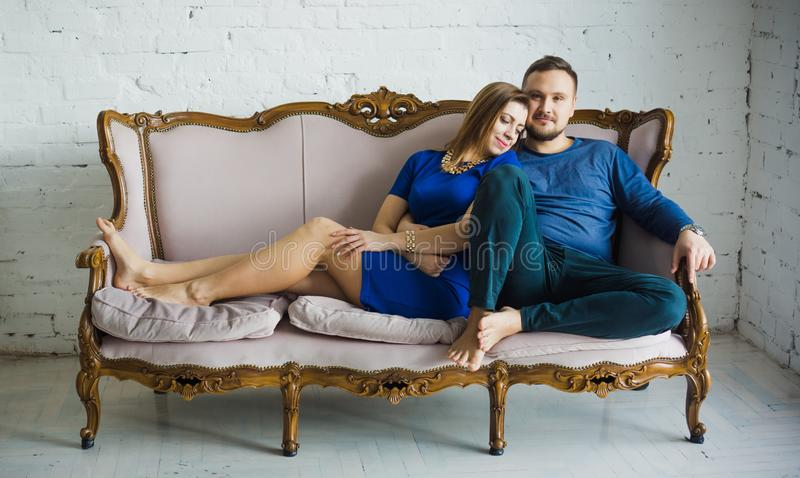 Ritratto di una coppia alla moda alla moda che si siede insieme ai piedi nudi sullo strato nel salone, abbracciando, sorridendo, immagine stock