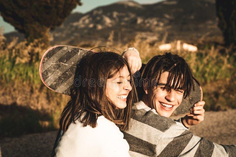 Ritratto di una coppia con i skateboarder di divertimento e felici fotografia stock