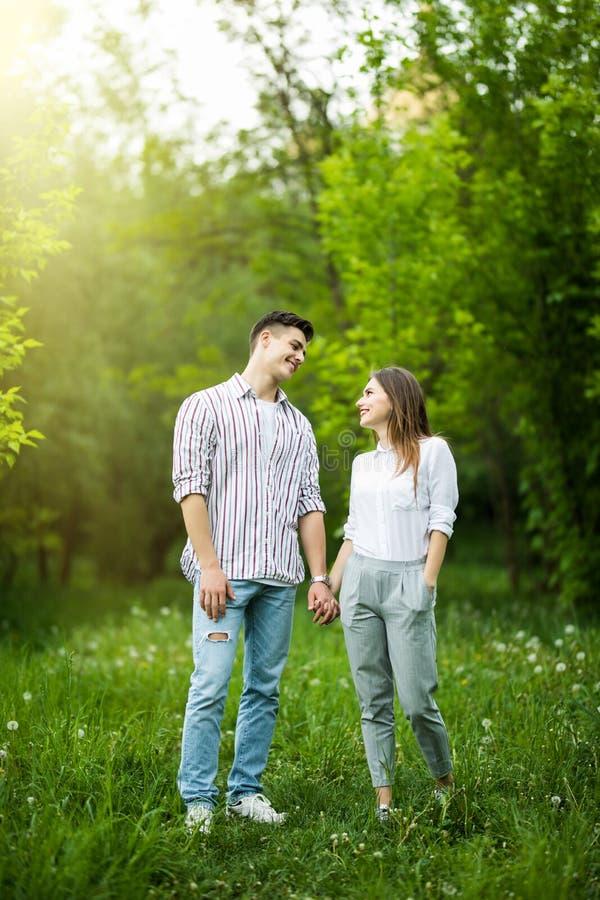 Ritratto di una coppia felice che cammina insieme all'aperto nel parco verde immagini stock