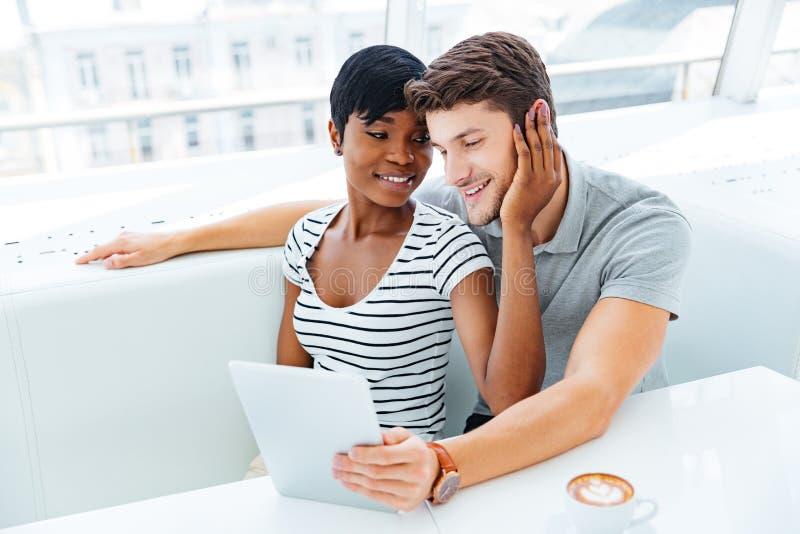 Ritratto di una coppia felice facendo uso del computer della compressa in ristorante immagini stock libere da diritti