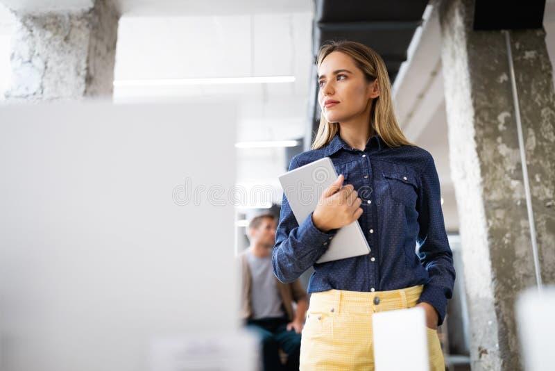 Ritratto di una designer sorridente, studentessa e imprenditrice freelancer che usa un tablet computer fotografia stock libera da diritti